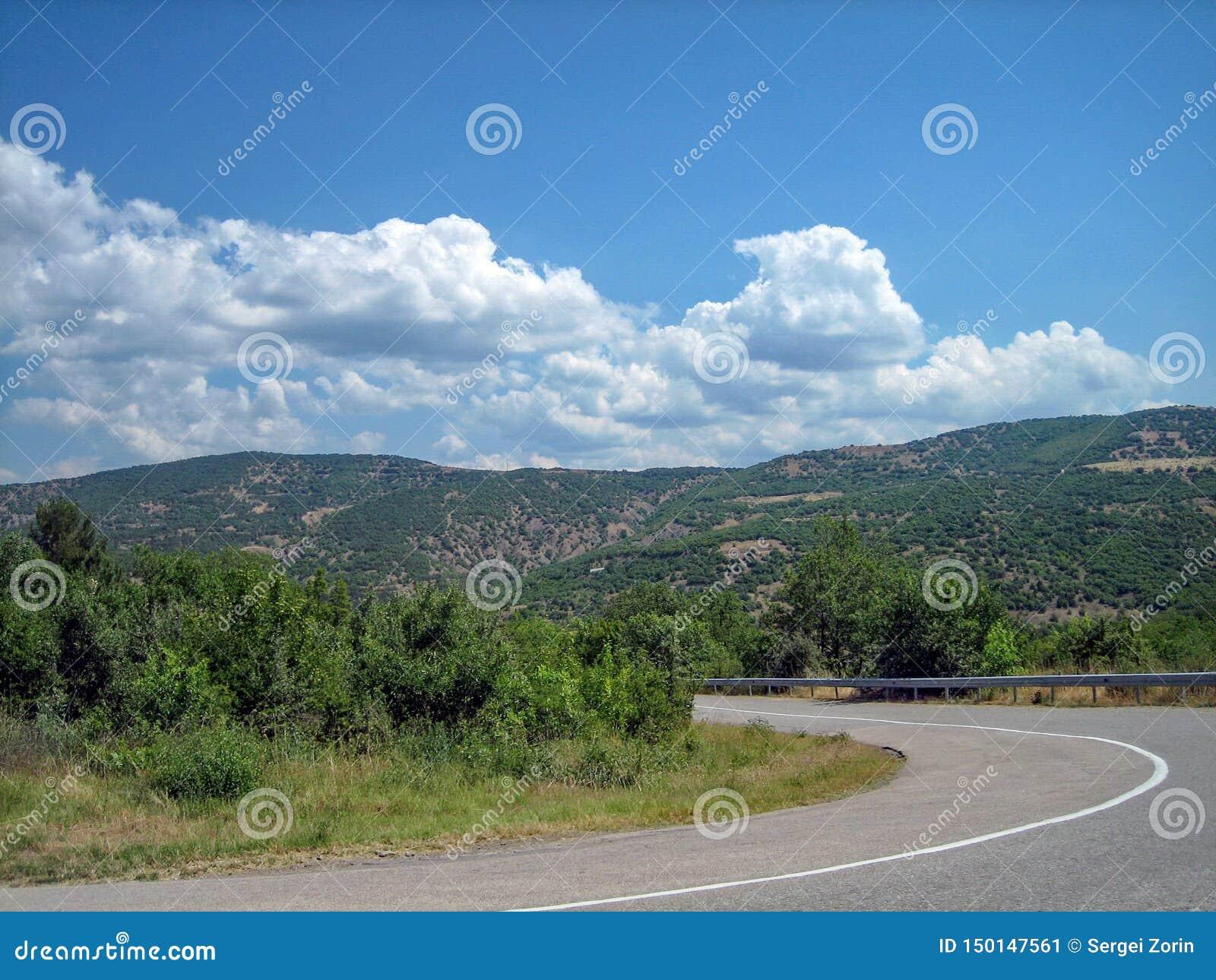 Пустая дорога в южной холмист-гористой зоне на горячий летний день
