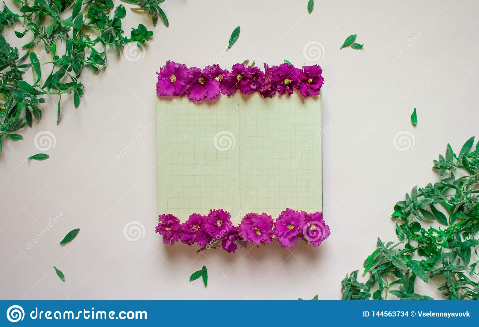 Пустая тетрадь украсила пурпурные цветки на белой предпосылке, взгляде сверху Блокнот украшенный с зелеными листьями и фиолетом r