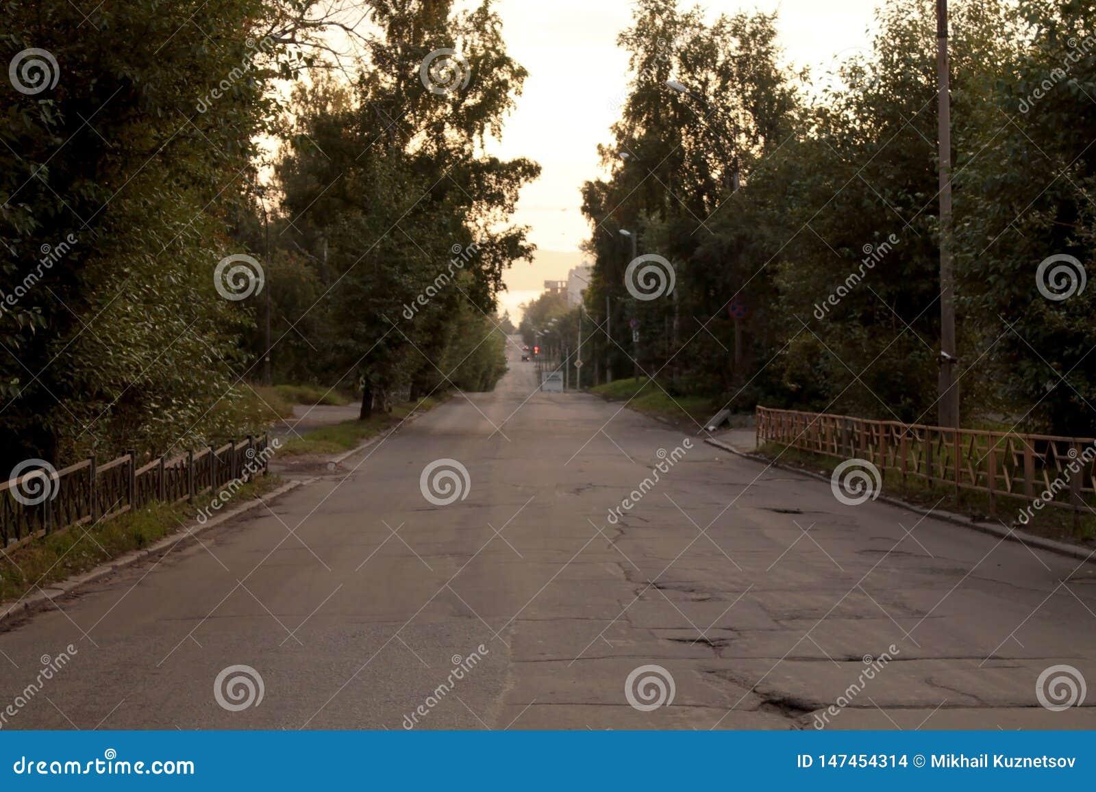 Пустая улица вечером с сельской плохой дорогой асфальта