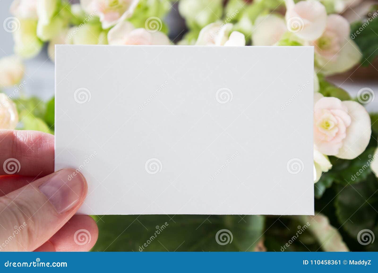 Пустой белый шаблон карточки посещения в руке ` s женщины с цветками на предпосылке Модель-макет
