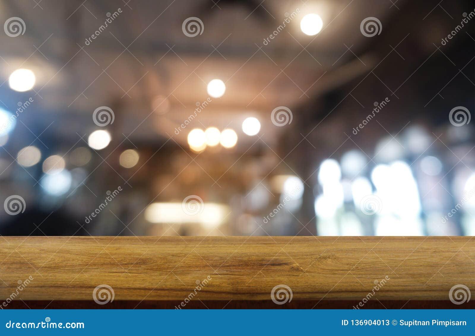 Пустой темный деревянный стол перед абстрактной запачканной предпосылкой интерьера ресторана, кафа и кофейни смогите быть использ