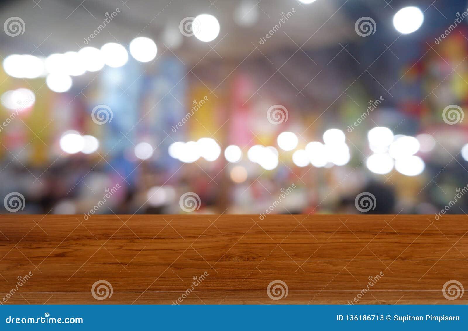 Пустой темный деревянный стол перед конспектом запачкал предпосылку интерьера кафа и кофейни Смогите быть использовано для диспле