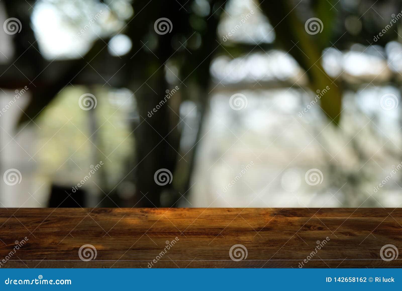 Пустой темный деревянный стол перед конспектом запачкал предпосылку bokeh ресторана