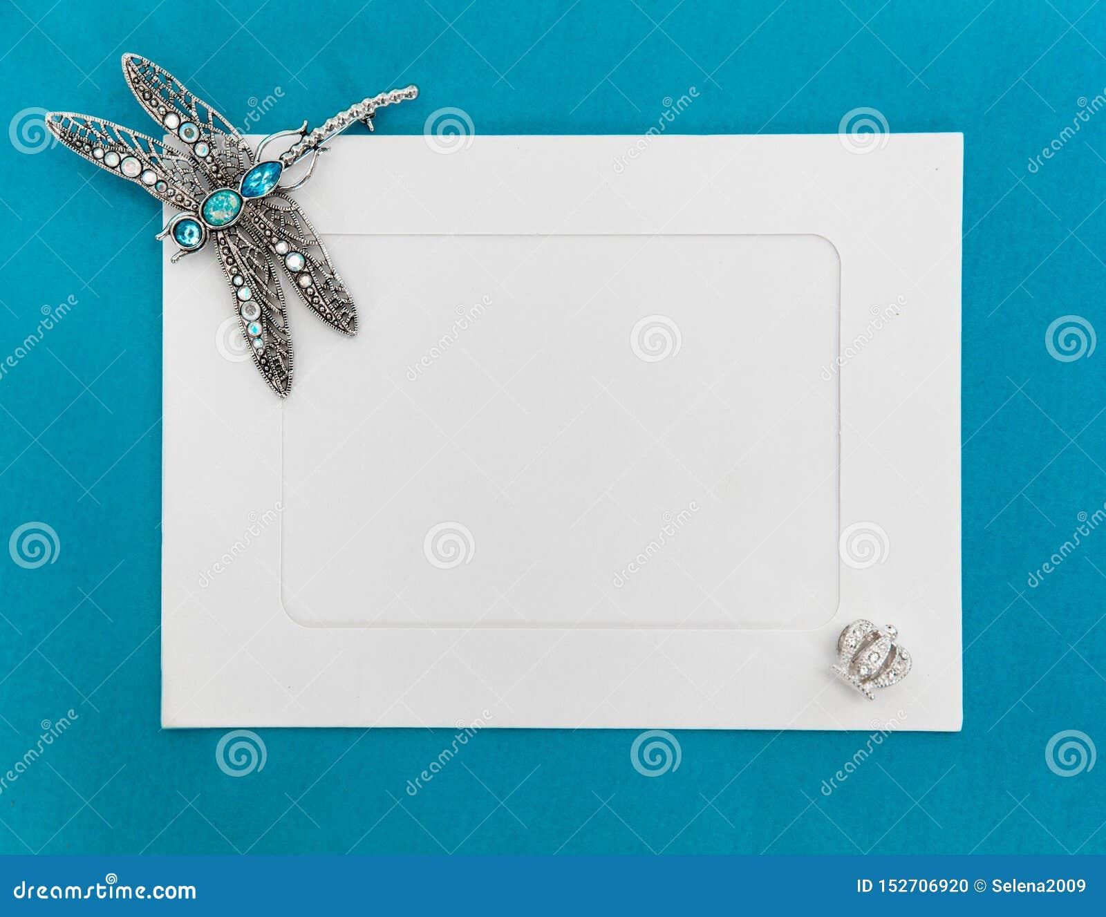 Пустой шаблон с рамкой белой бумаги на голубой предпосылке, украшенной с ювелирными изделиями Серебряная фибула dragonfly на угле