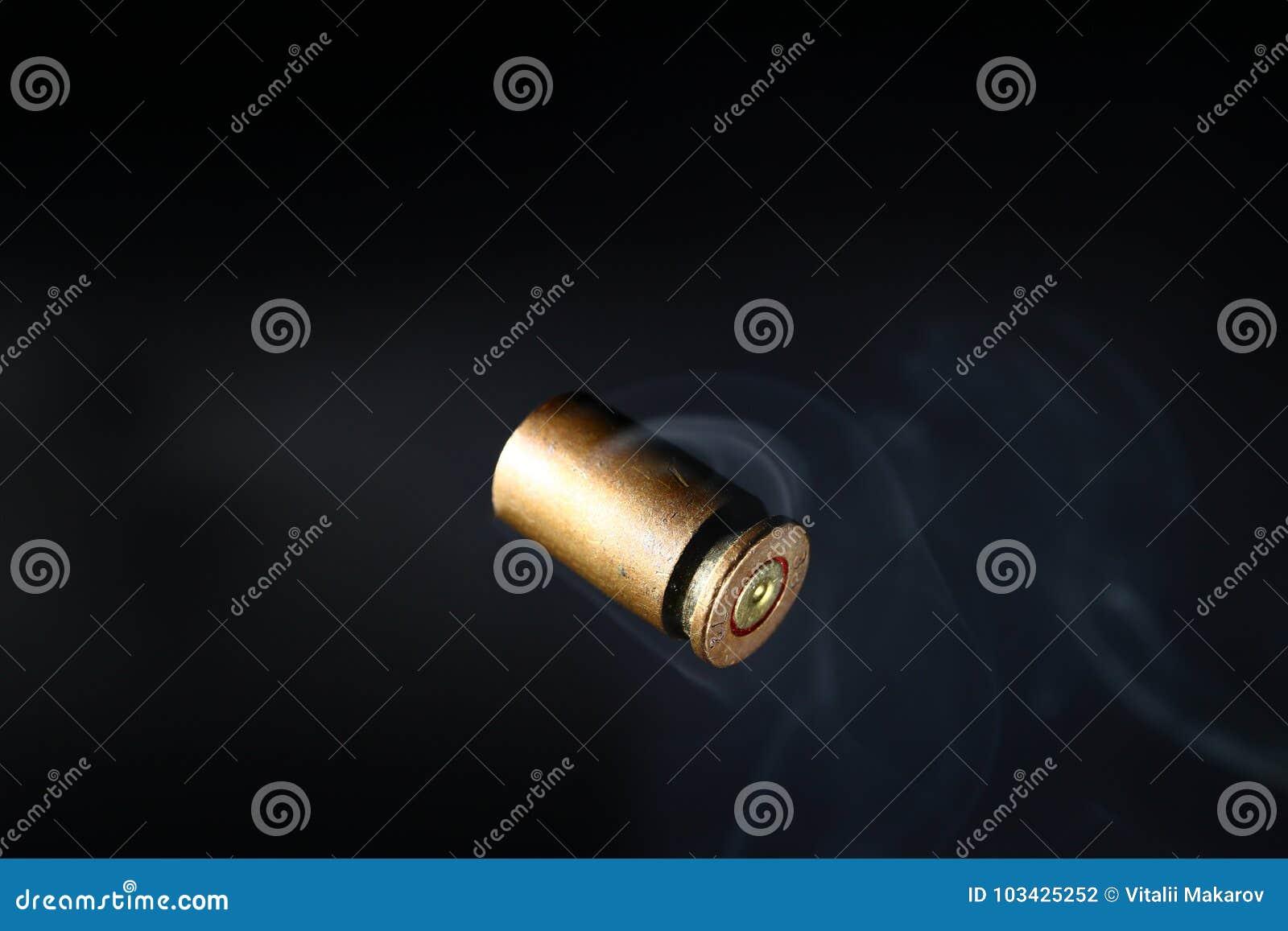 Пустые кожухи раковины пули, на черной предпосылке, курят