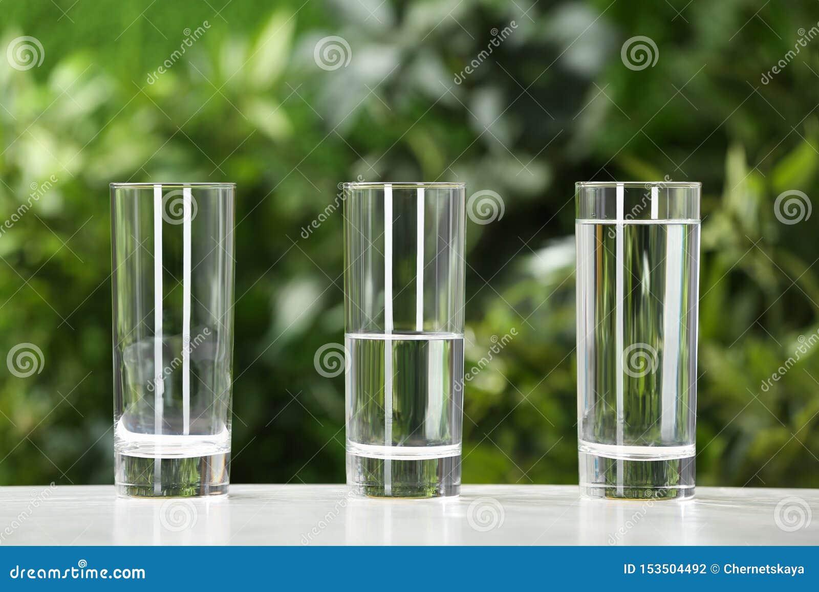 Пустые, половинные и полные стекла воды на белой таблице