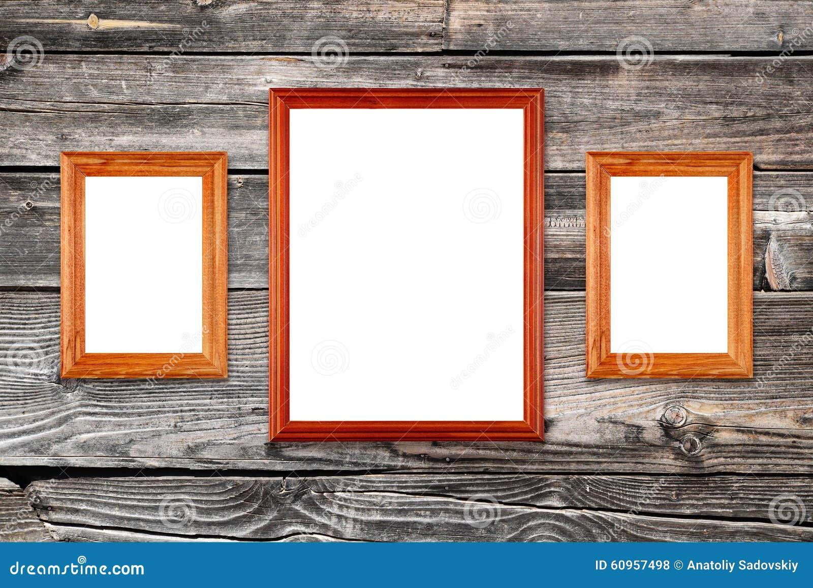 Пустые рамки фото на деревянной стене