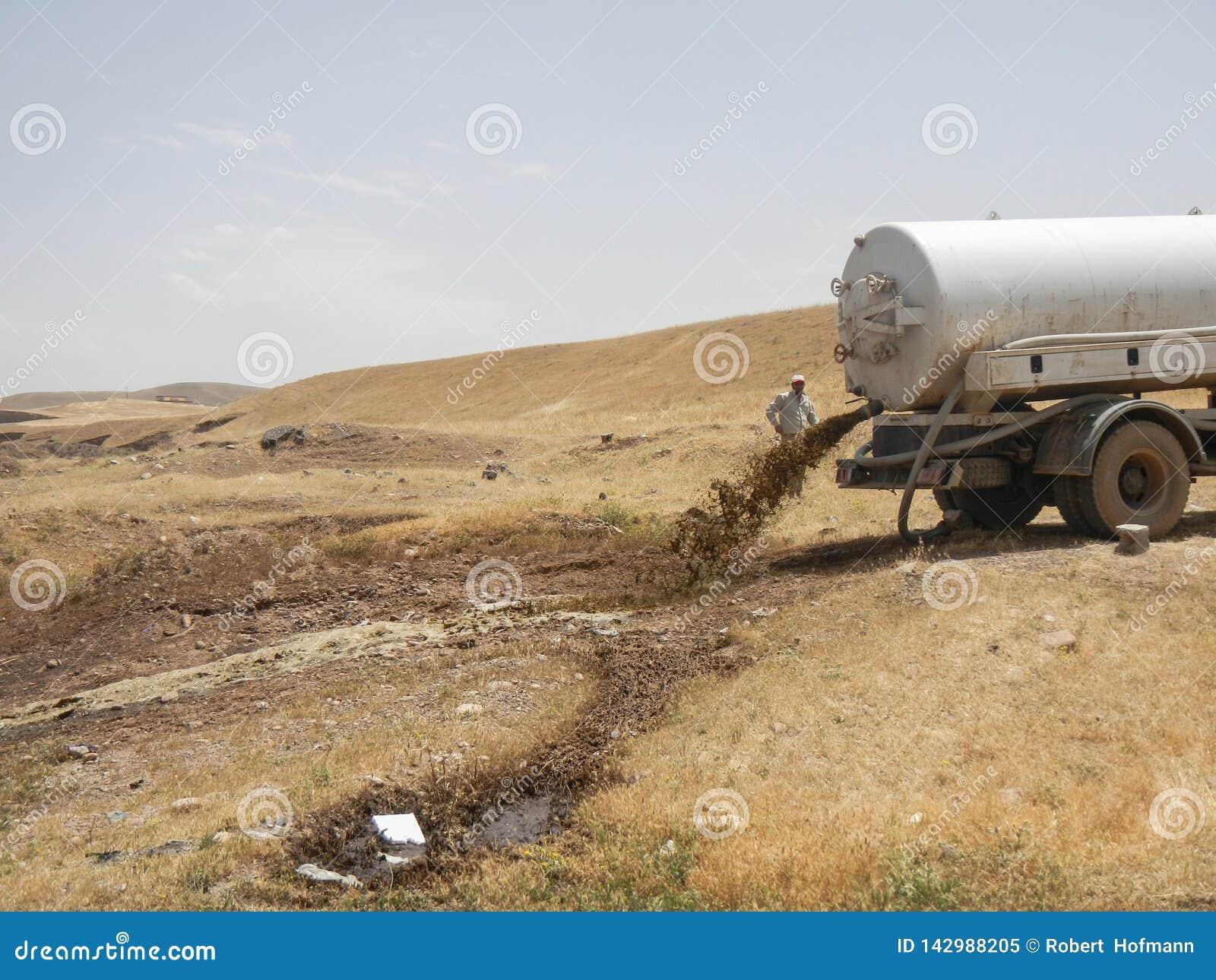 21 05 2017, пустыня вне лагеря Kawergosk, Ирака : Тележка нечистот сбрасывает свою нагрузку вне лагеря беженцев Kawergosk внутри