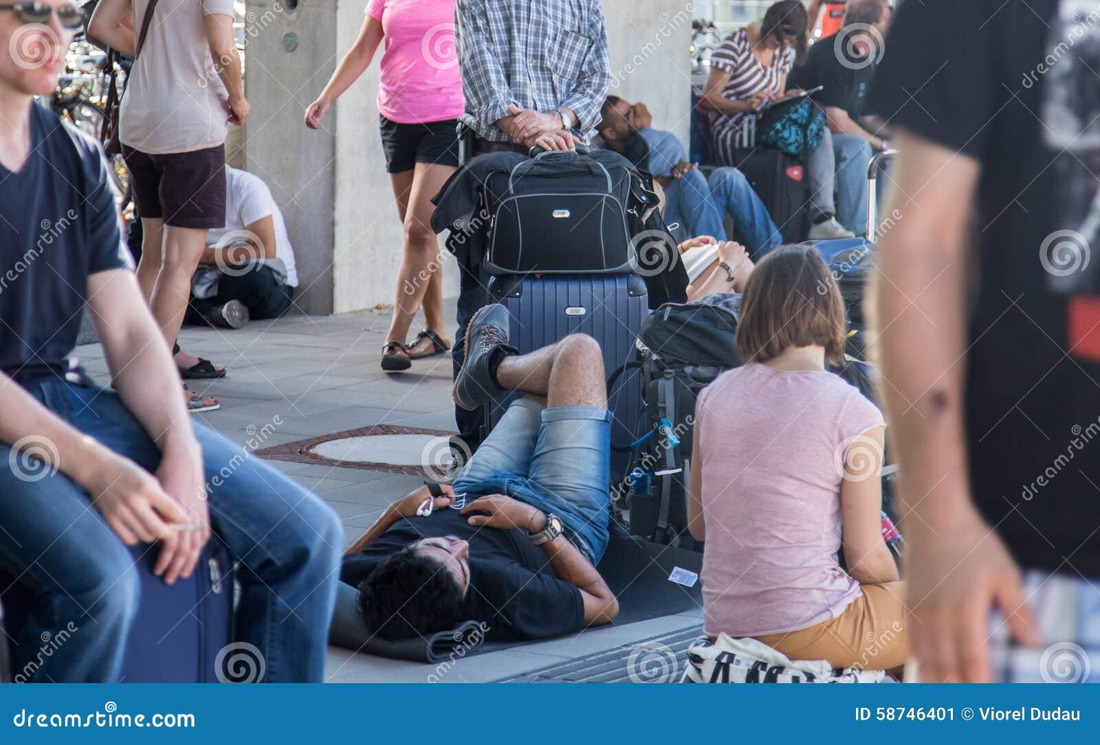 Путешественники ждать поезд в переполненной станции