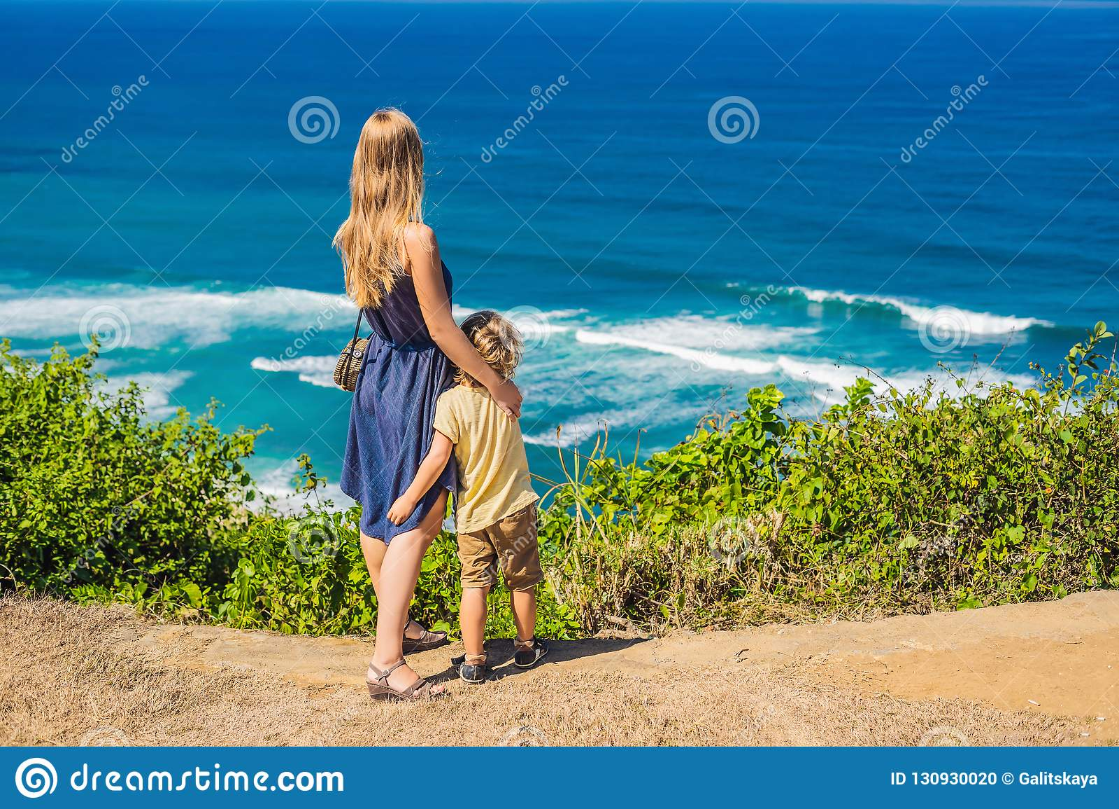 Путешественники мамы и сына на скале над пляжем Пустой рай
