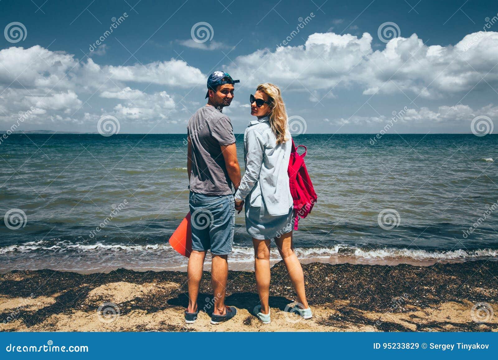 Путешественники человек и женщина пар стоя на Seashore и взглядах на концепции путешествием перемещения приключения камеры