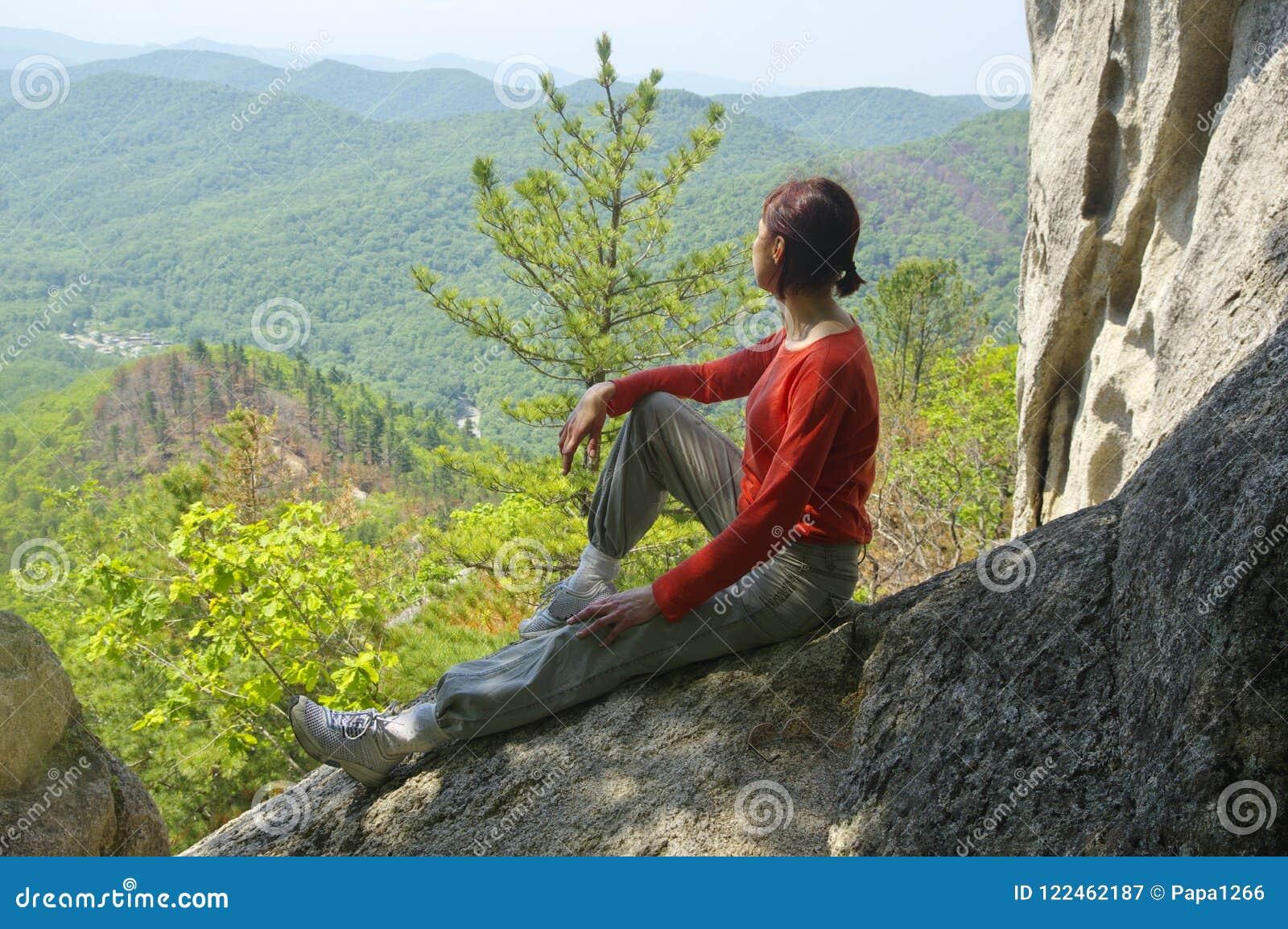 Путешественник женщины сидит и смотрит долина