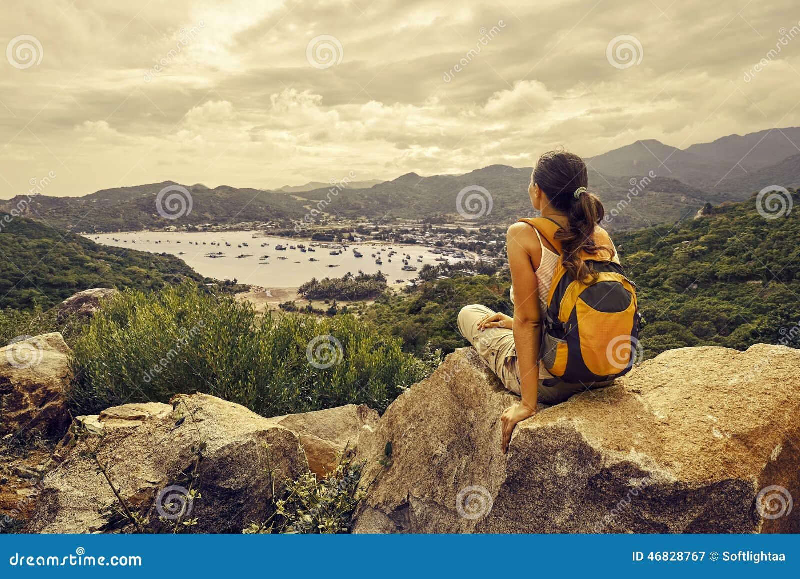 Путешественник женщины сидит и смотрит край скалы на заливе моря