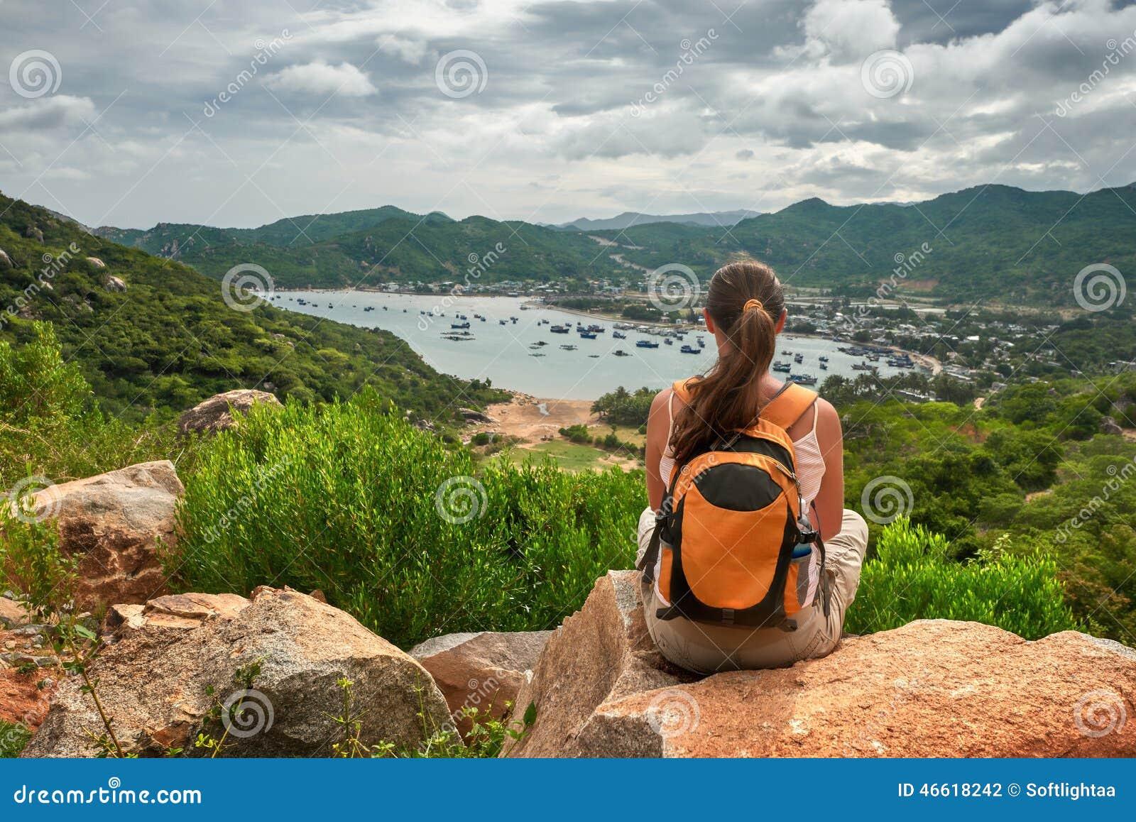 Путешественник женщины сидит и смотрит край скалы на s