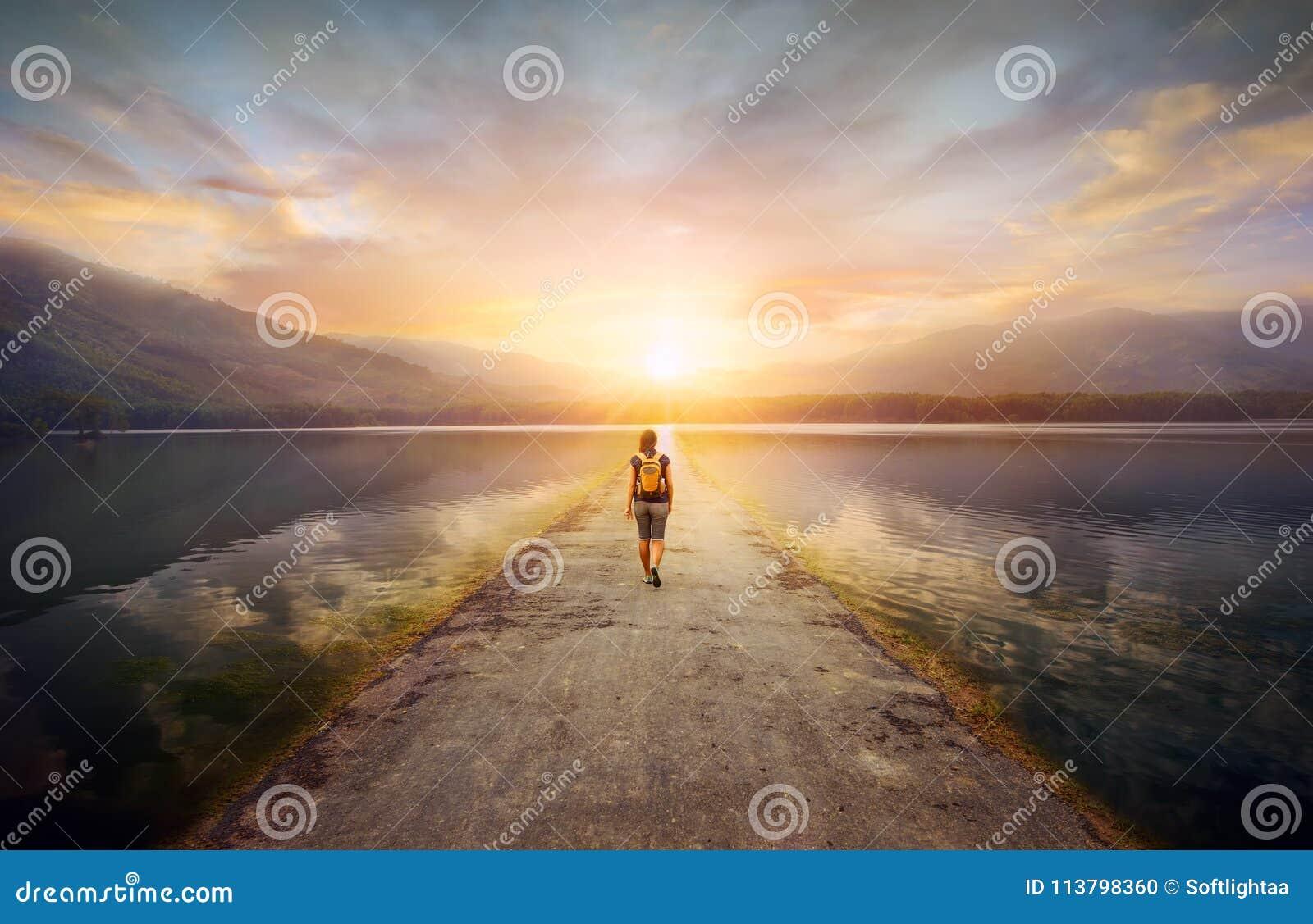 Путешественник идя вдоль дороги к горам
