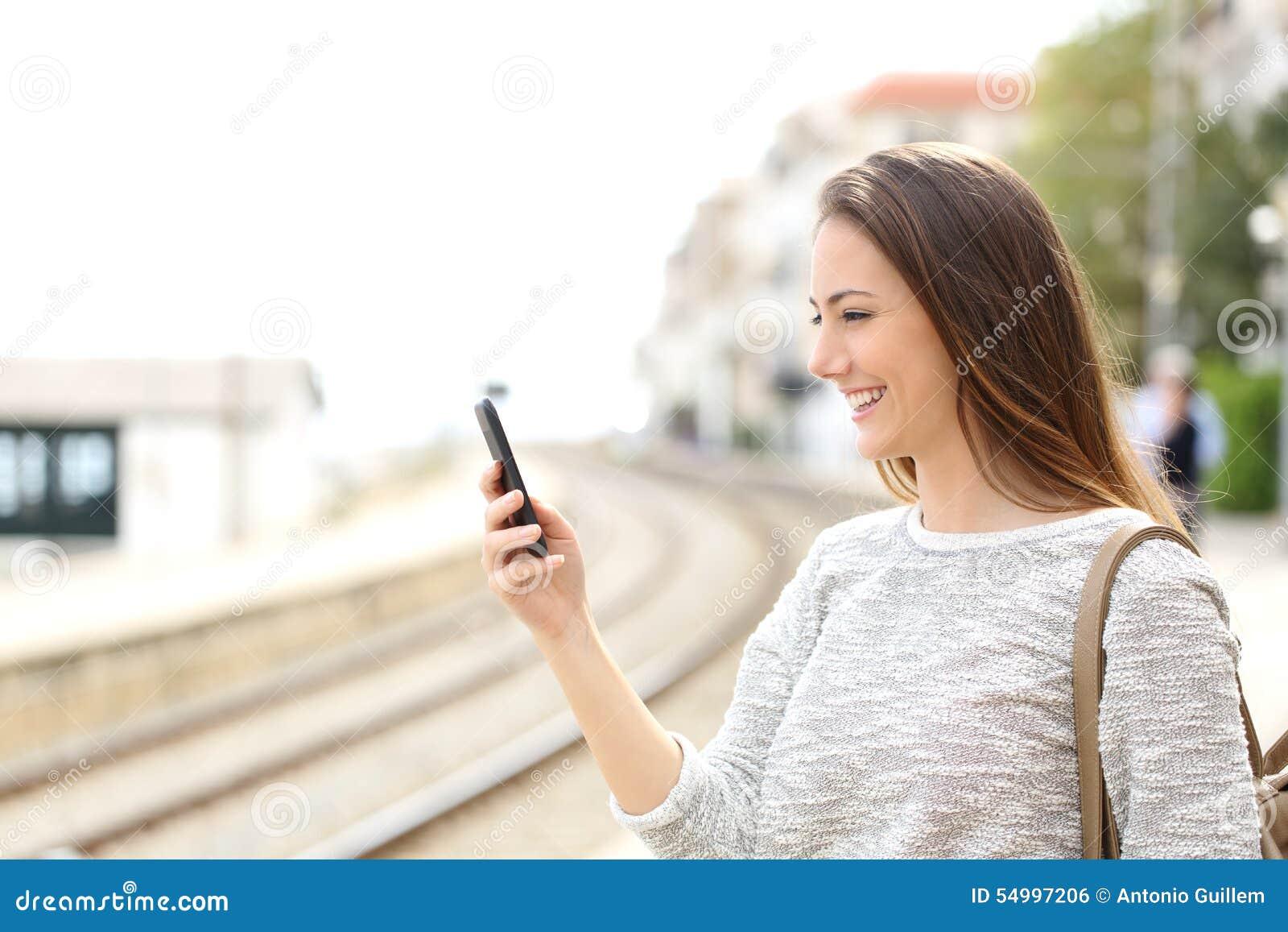 Путешественник используя smartphone в вокзале
