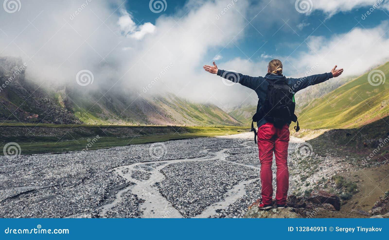 Путешественник молодого человека идя и наслаждается взглядом moun весны лета