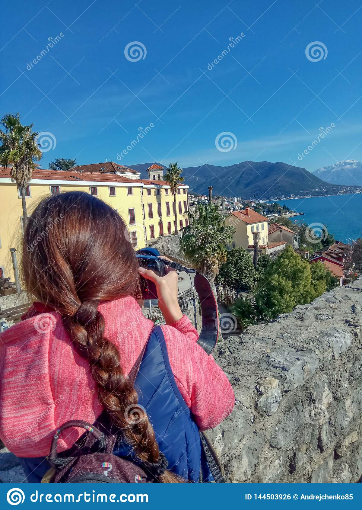 Путешественник молодой женщины фотографируя с городом и горами профессиональной камеры фото старым