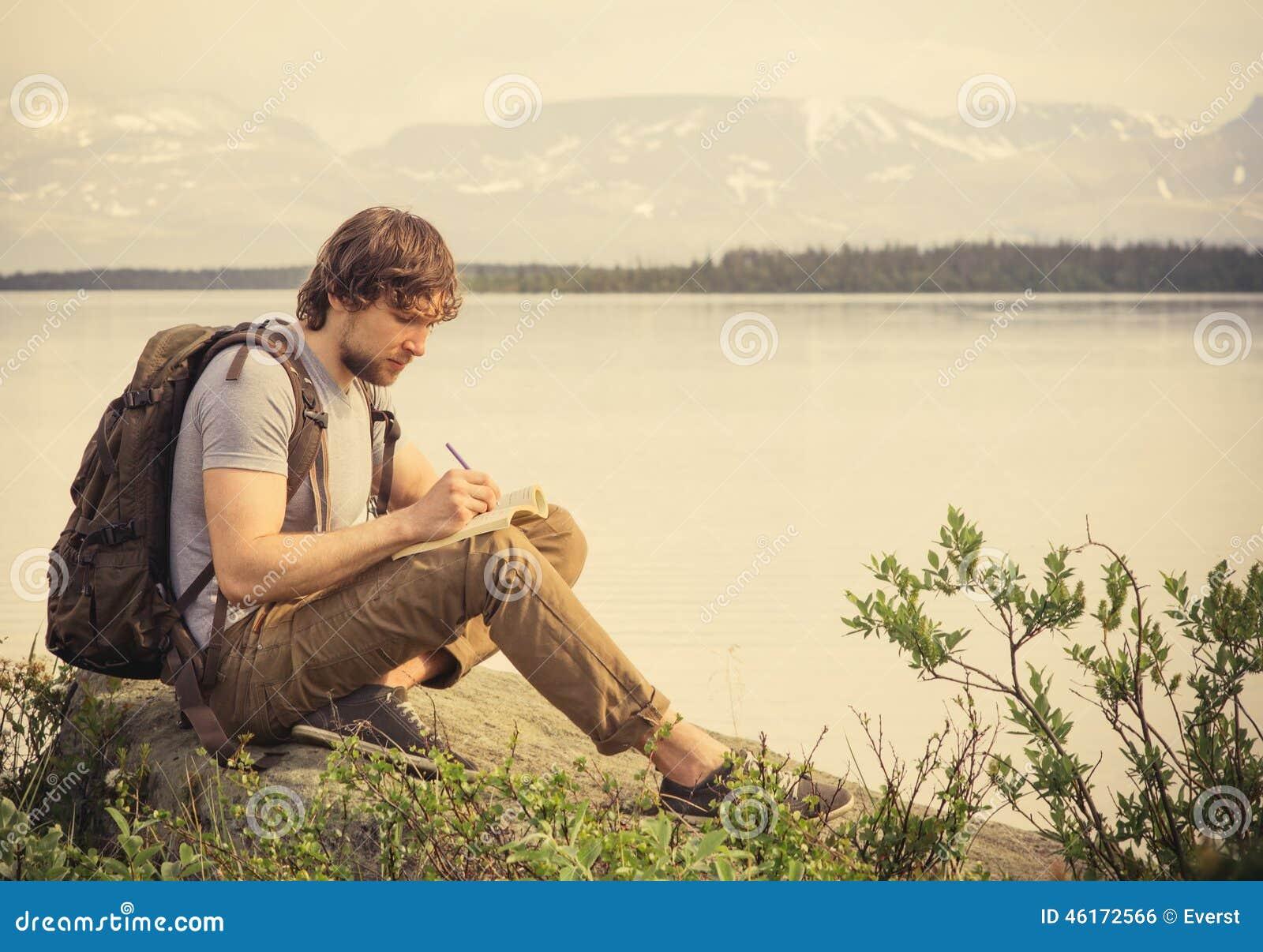Путешественник молодого человека с книгой чтения рюкзака