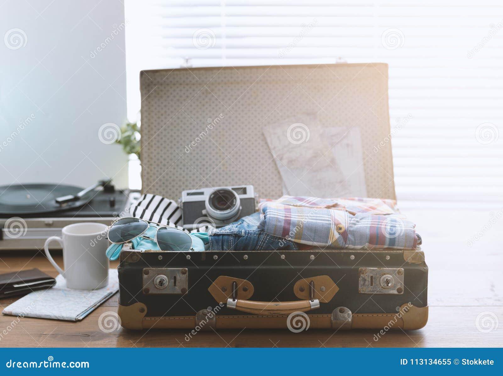 Путешественник пакуя его чемодан перед выходить