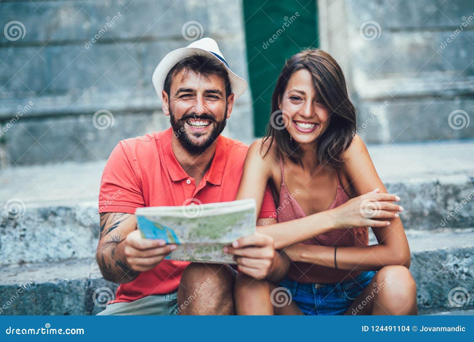Путешествовать пары туристов идя вокруг старого городка
