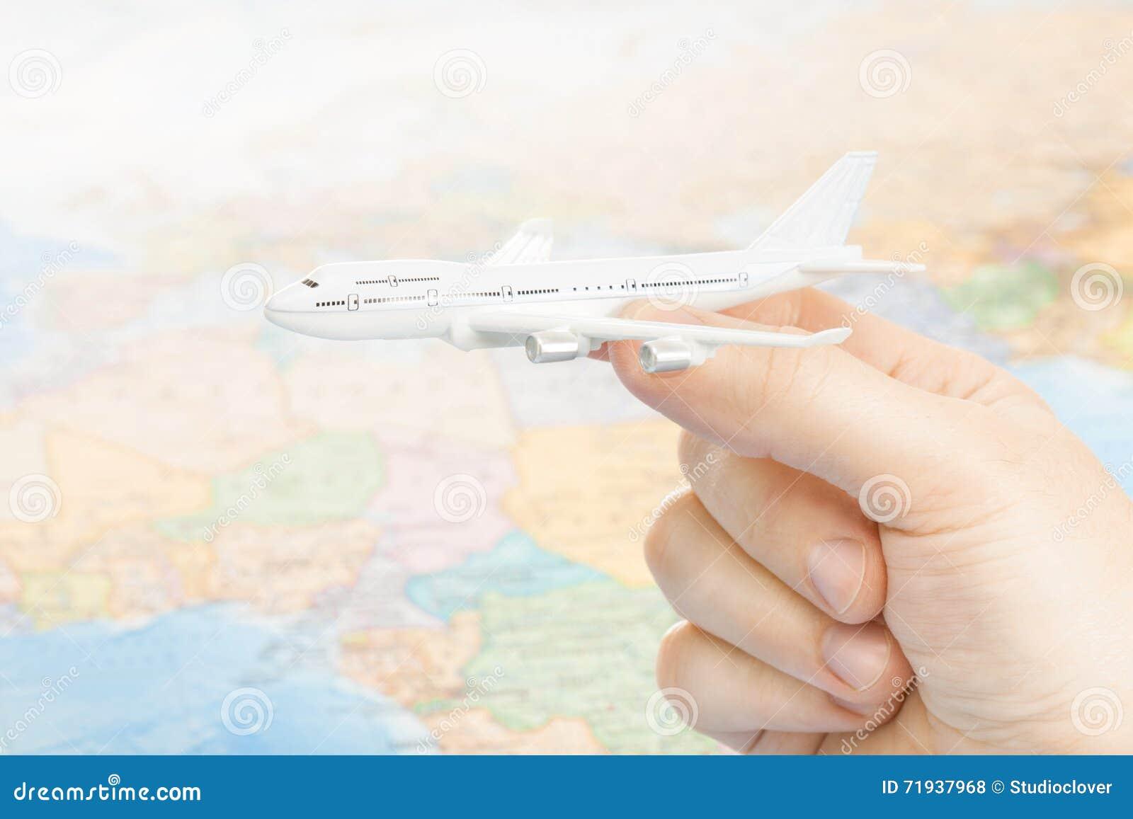 Путешествовать, туризм, сообщения и все вещи связали - съемка студии aircarft игрушки в руке с картой мира на предпосылке