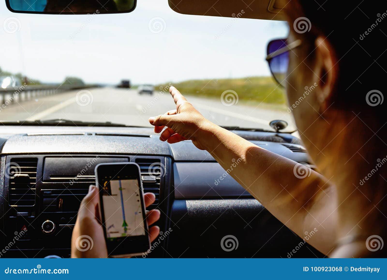 Путешествуйте в концепции автомобиля, smartphone выставок девушки в ее руке с раскрытой навигацией app gps