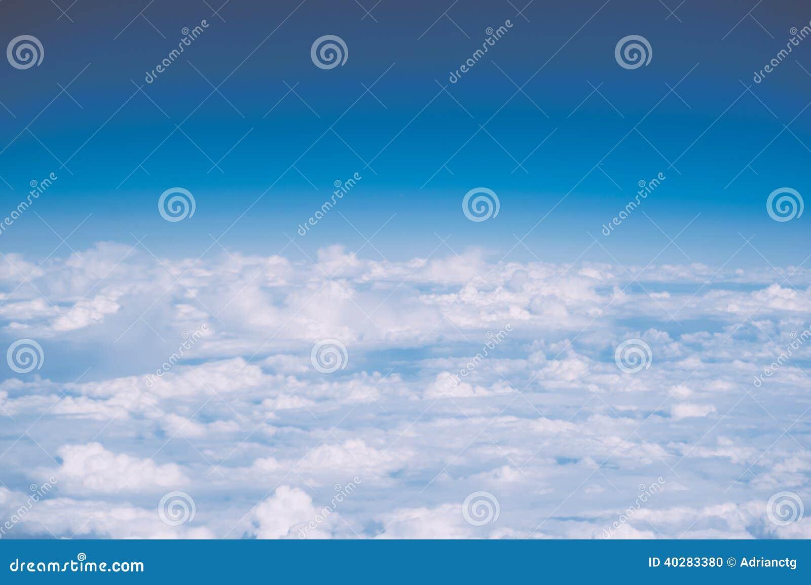 Пушистые белые облака и голубое небо с космосом экземпляра, взглядом самолета