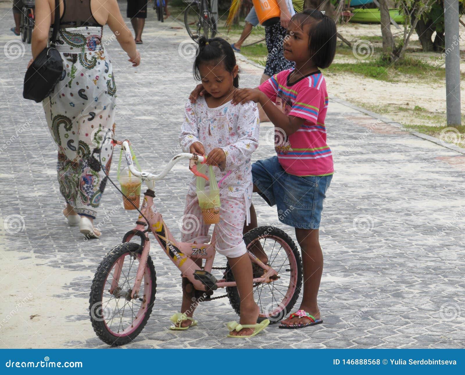 Пхукет, Пхукет Таиланд - 10 15 2012: темнокожая азиатская девушка держит ее друга плечами который занятый с ее велосипедом