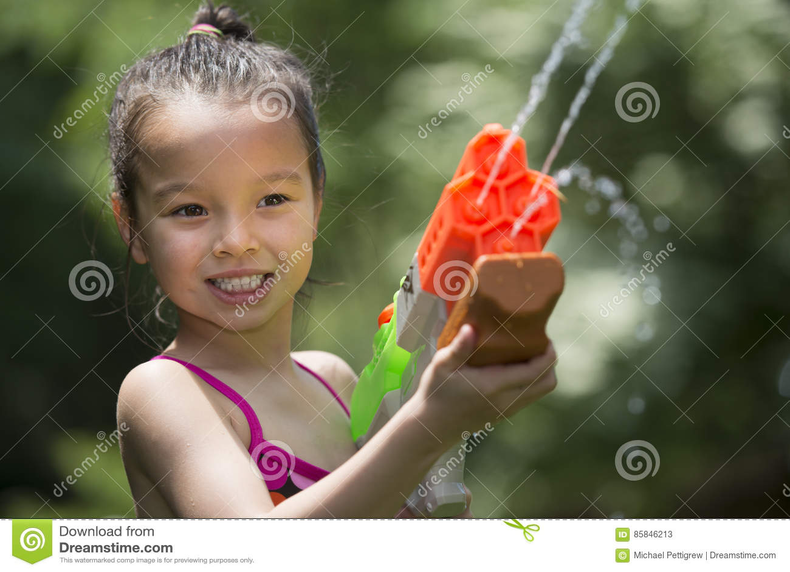Пятилетняя старая девушка играя с squirt игрушка