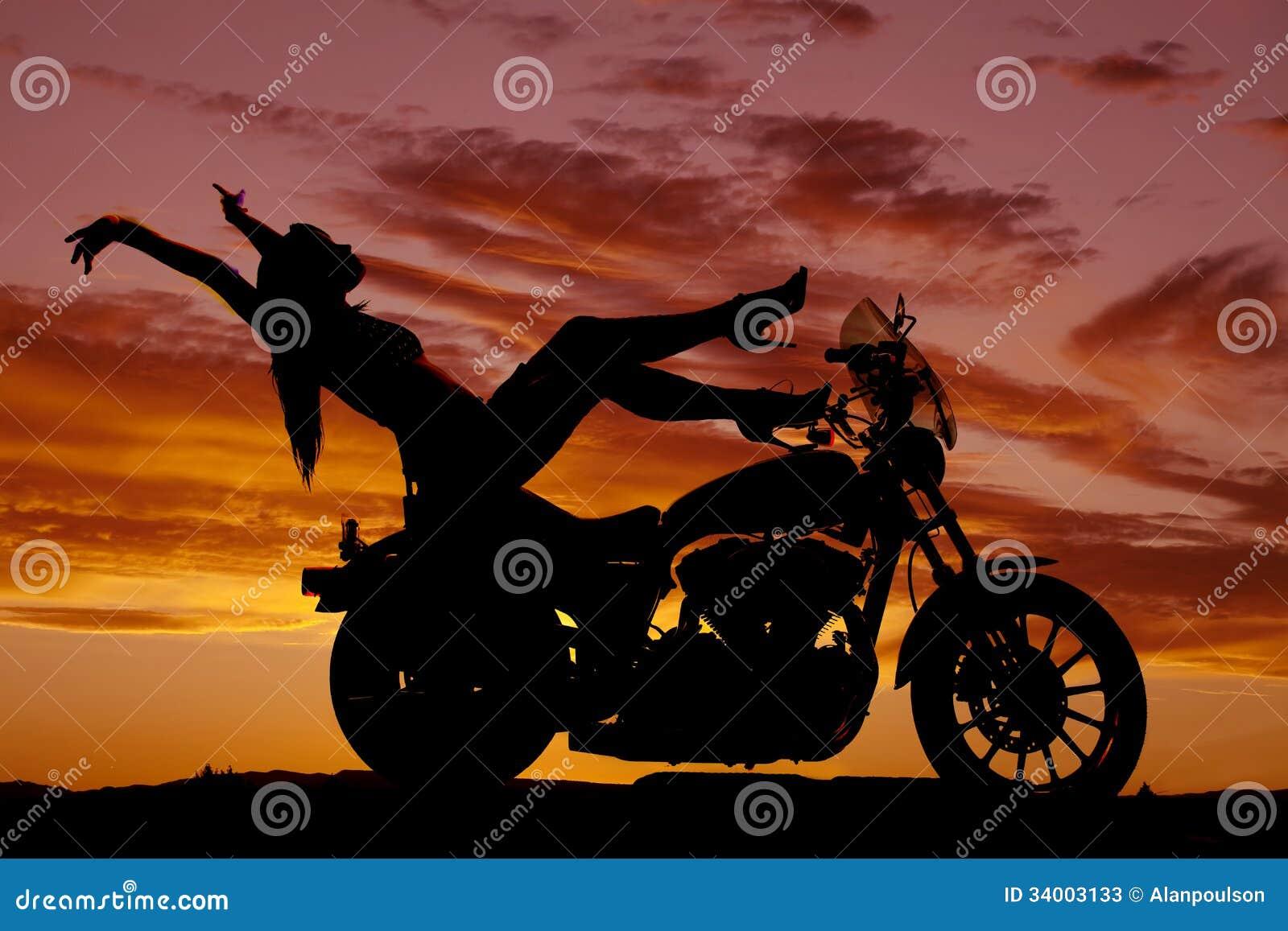 Пятки мотоцикла женщины силуэта поднимают руки назад