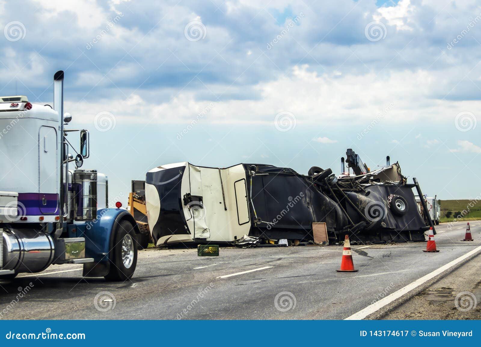 Пятое колесо RV переворачивало на шоссе с тележкой wench пробуя получить его вне дороги и 2 полуфабрикаты припарковали конусы бли