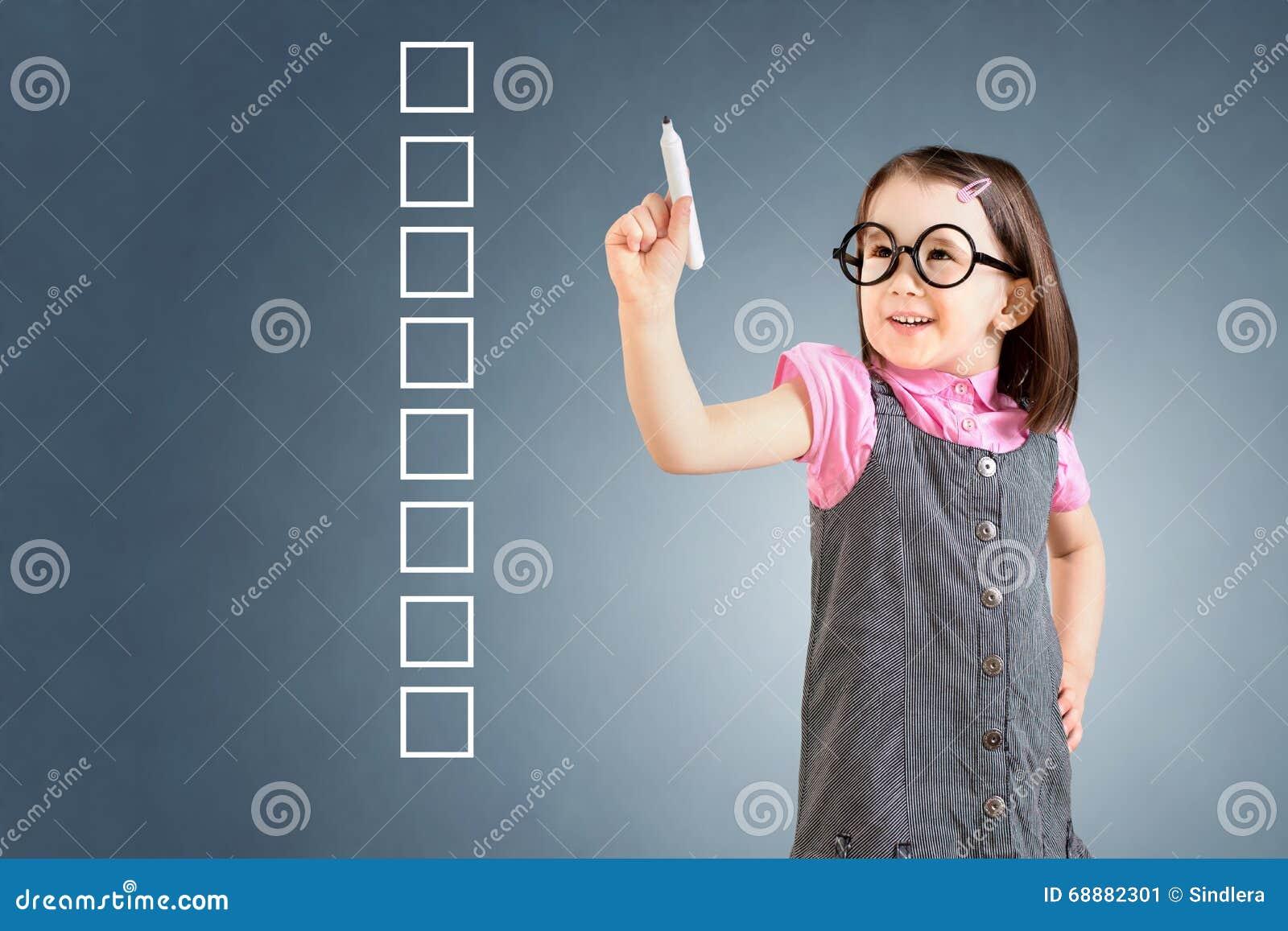 Платье дела милой маленькой девочки нося и запись на некоторых пустых коробках контрольного списока background card congratulatio