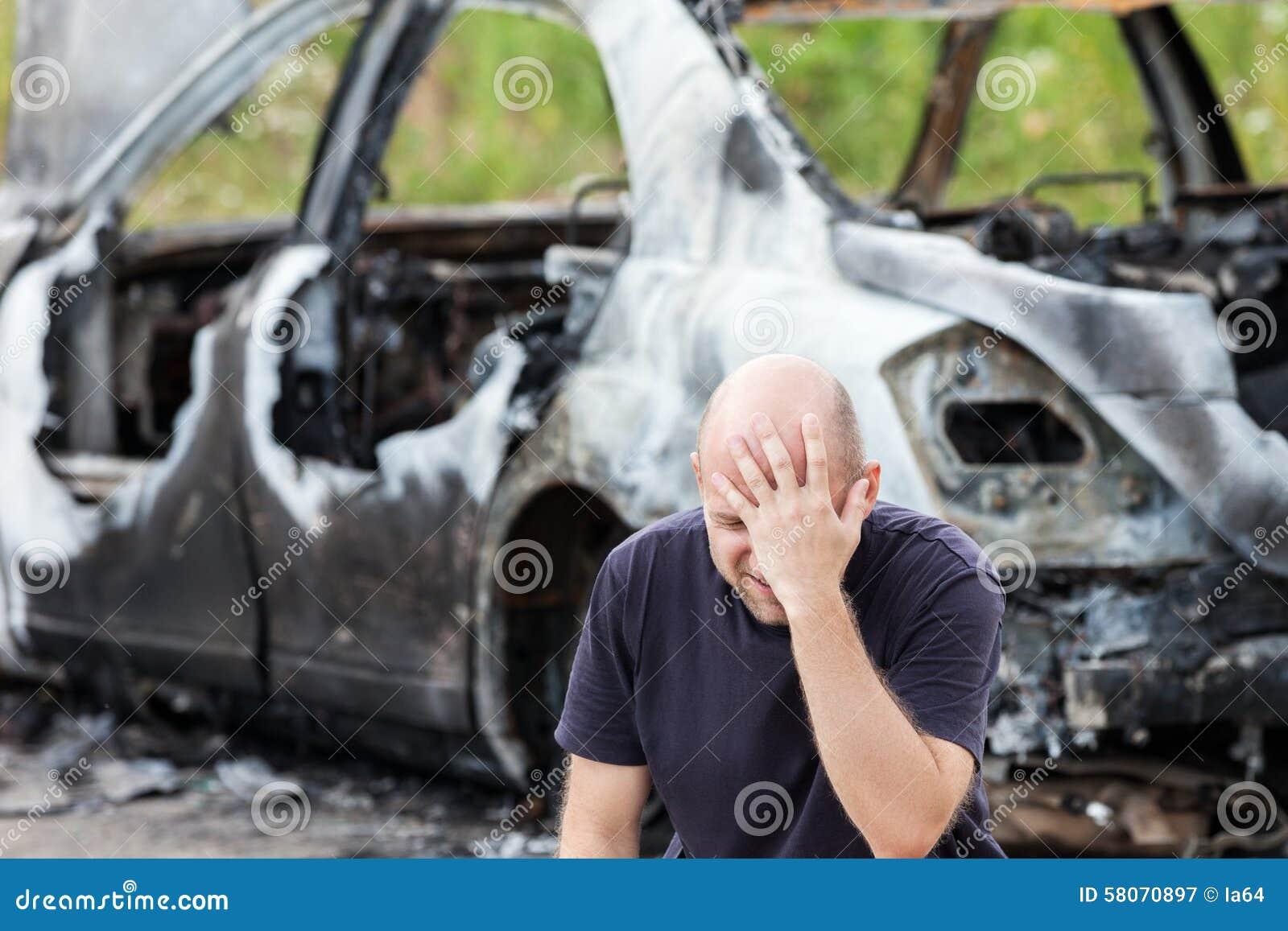 Плача расстроенный человек на огне поджога сгорел старье корабля автомобиля