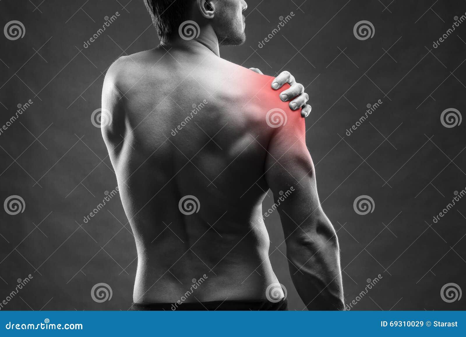 плечо боли мужчина тела мышечный Красивый культурист представляя на серой предпосылке