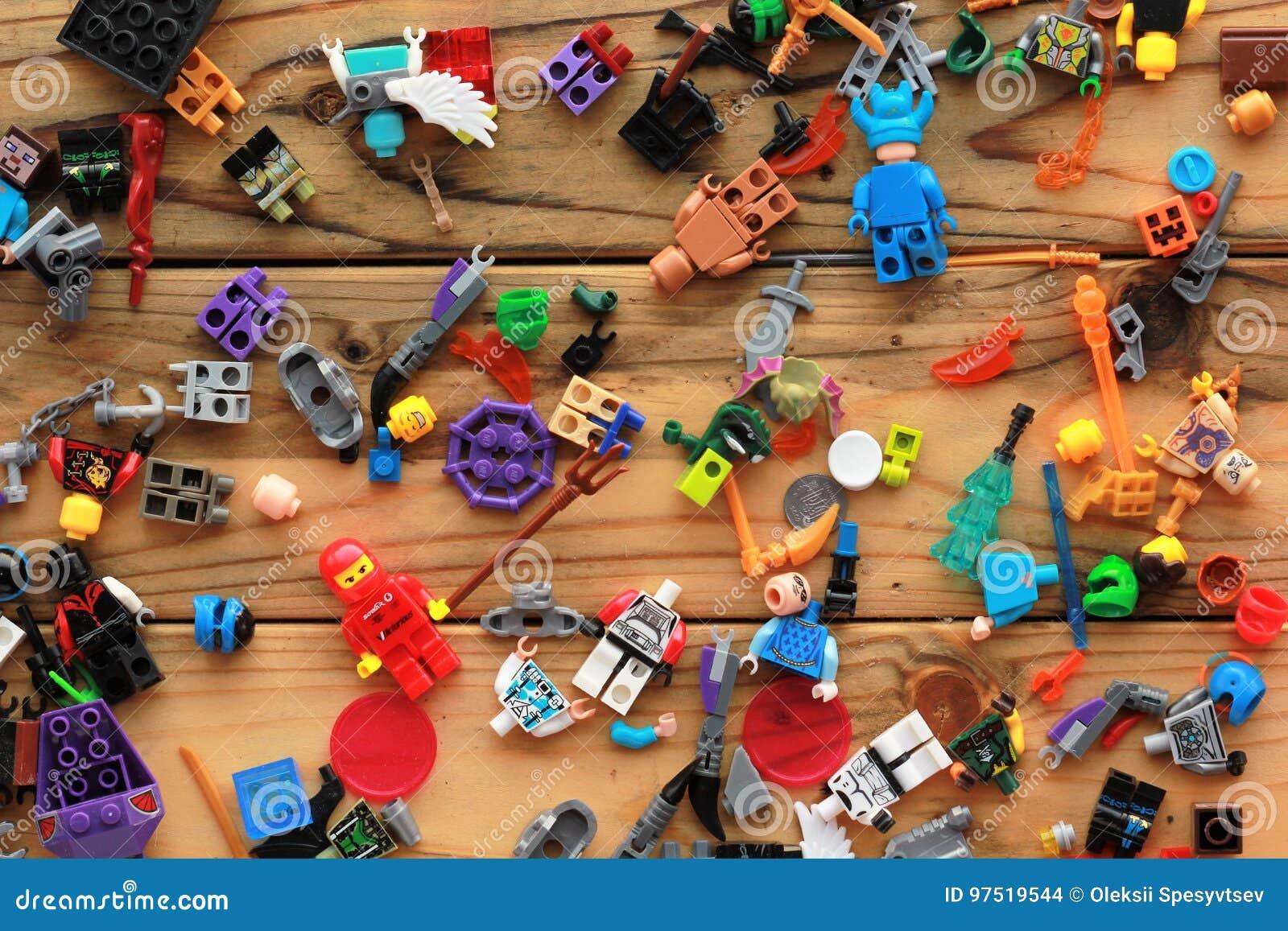 Плоское положение игрушек Lego разбросало на деревянный стол