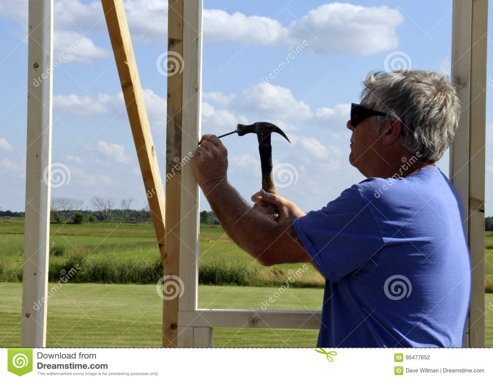 Плотник пригвождая с молотком