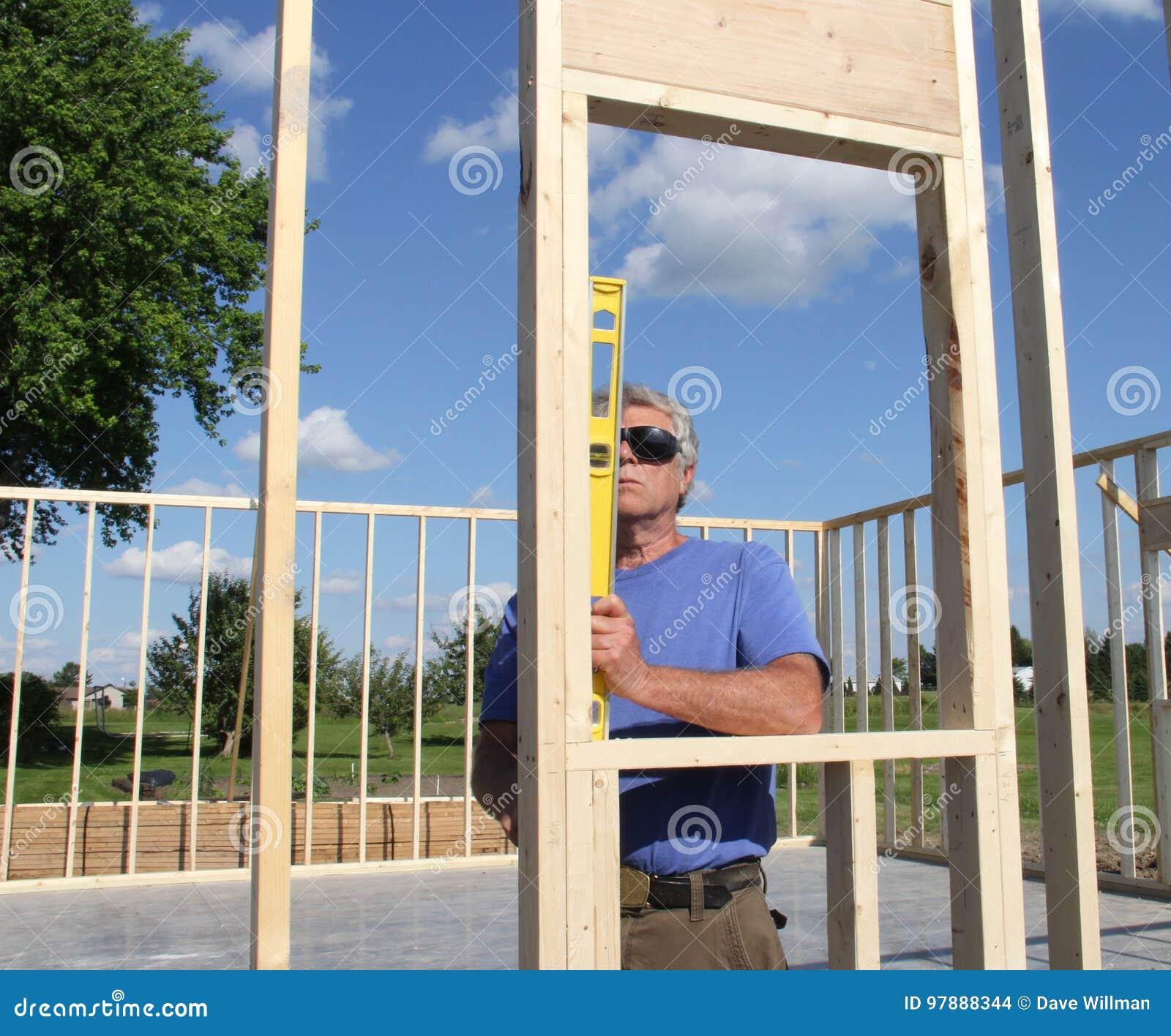 Плотник читая уровень на рамке дома