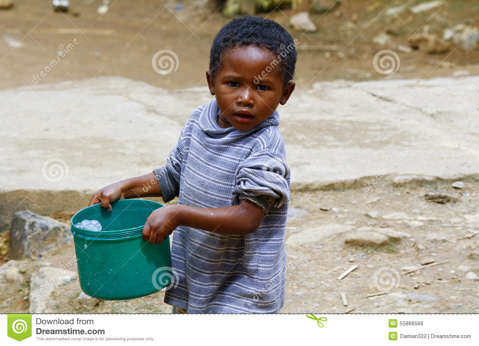 Плохой малагасийский мальчик нося пластичное ведро воды
