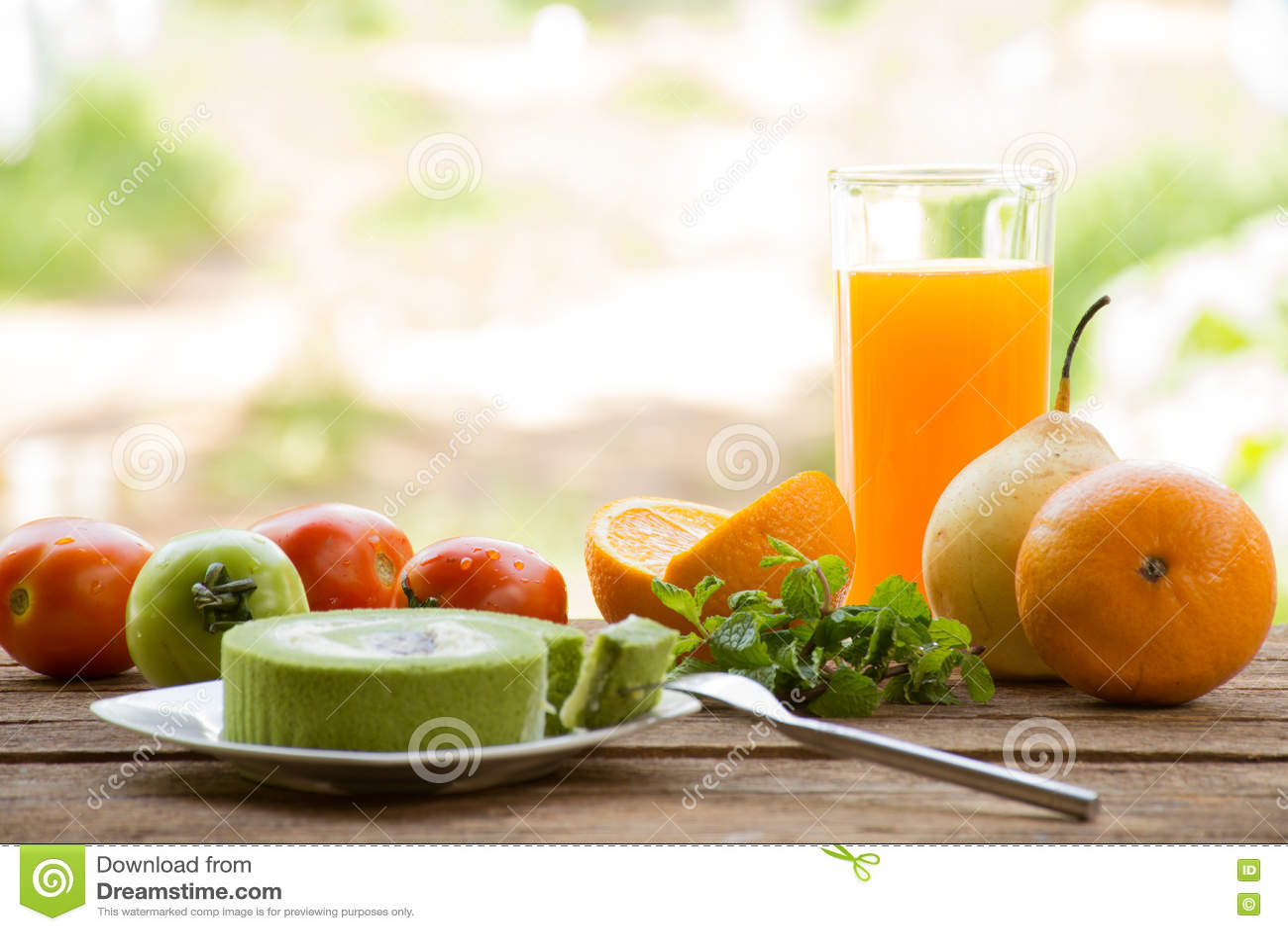 Плодоовощ предпосылки имеет томат и апельсин и сок с тортом зеленого чая На взгляде и празднике деревянной предпосылки внешнем с