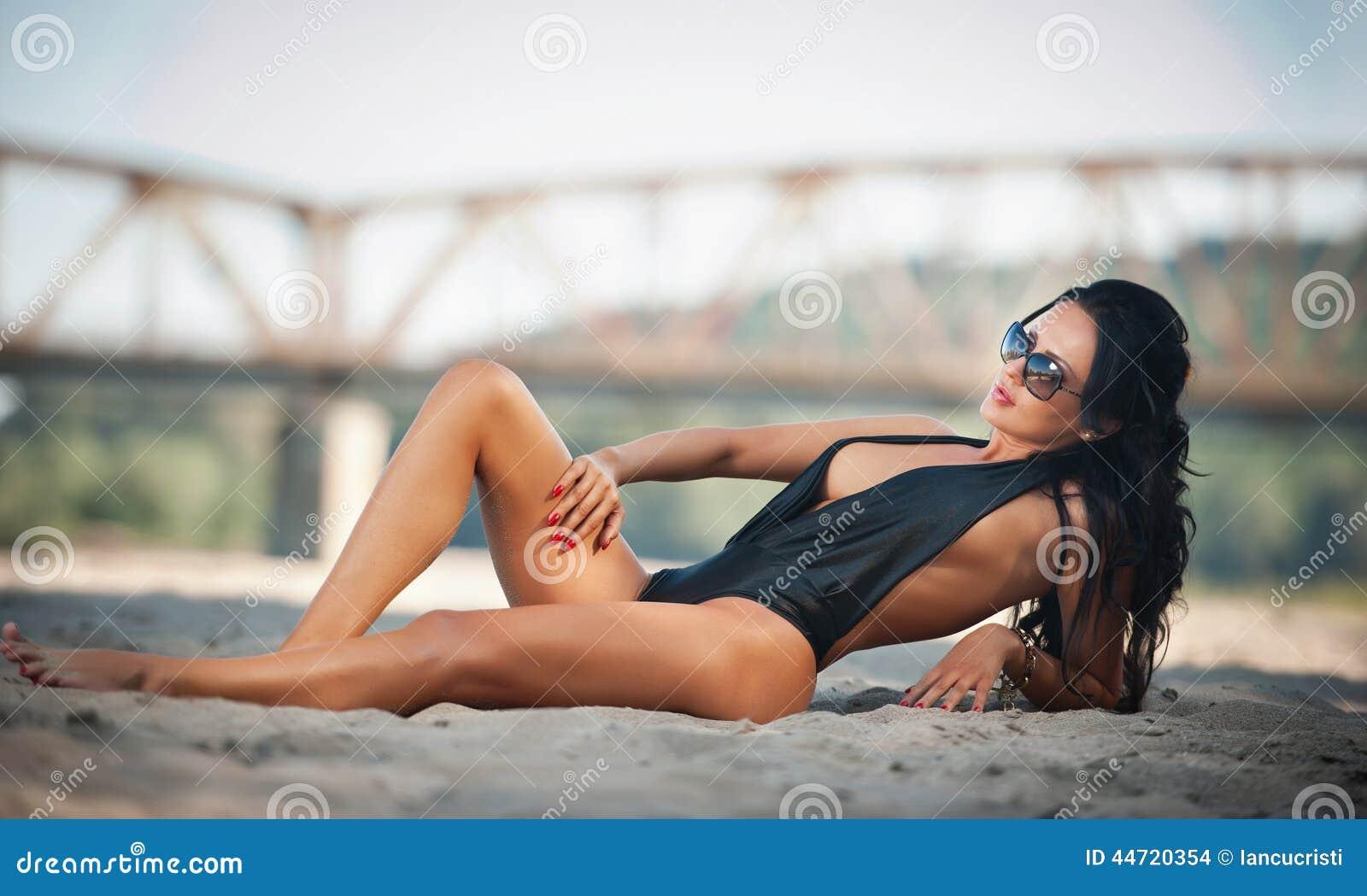 说谎在与一座桥梁的海滩的黑低胸的泳装的在背景中
