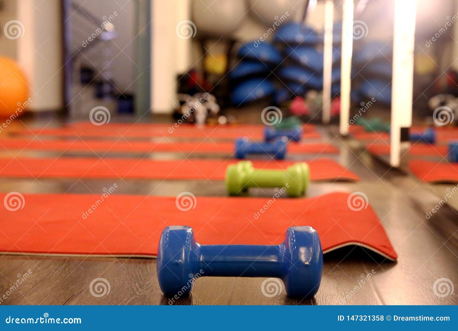 Работайте циновку и гантели в спортзале