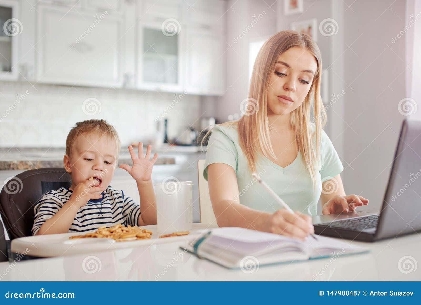 Работающая мать с ребенком в кухне