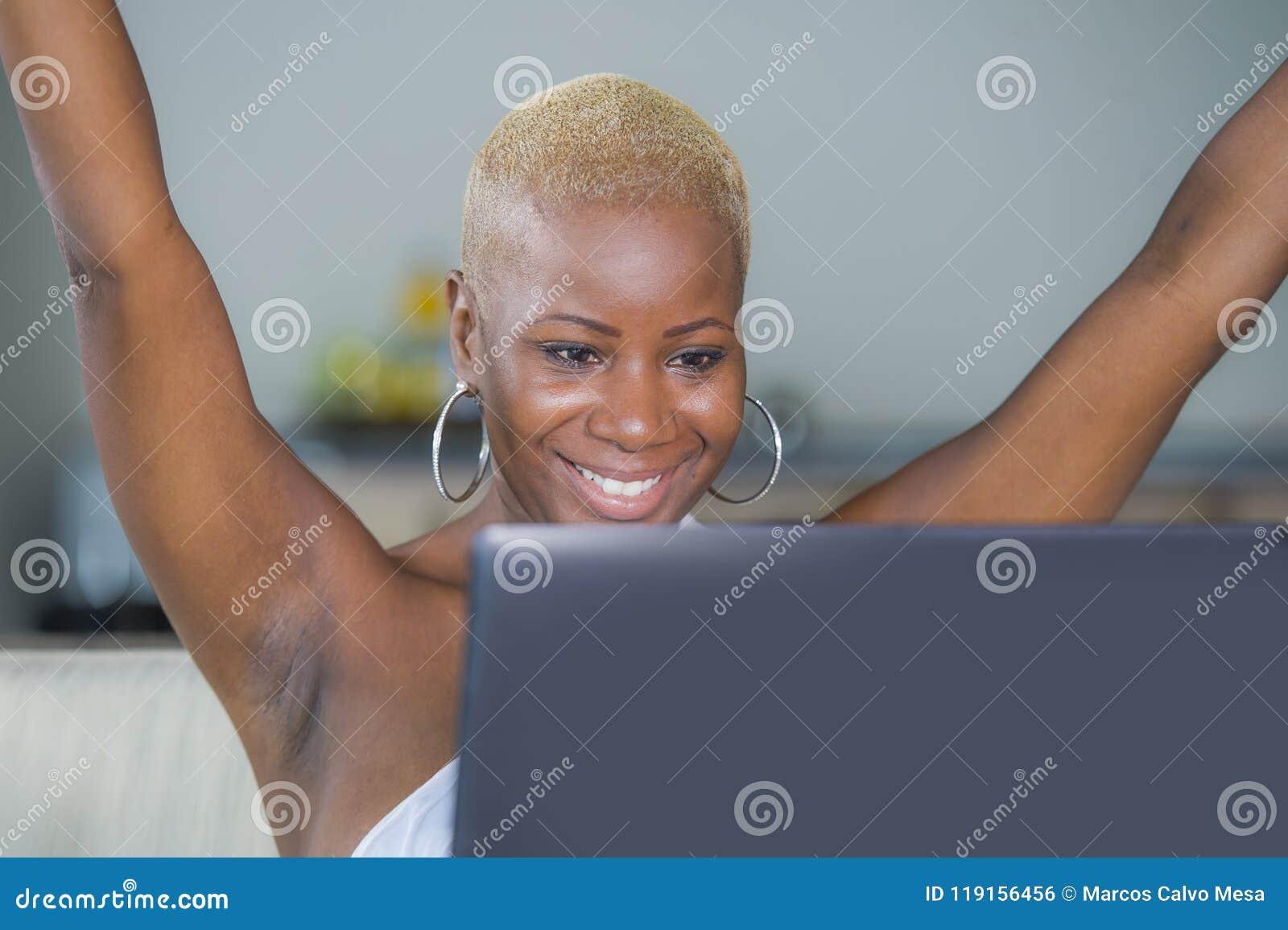 Работа молодой красивой счастливой черной афро американской женщины усмехаясь на портативном компьютере дома ослабила на кресле с