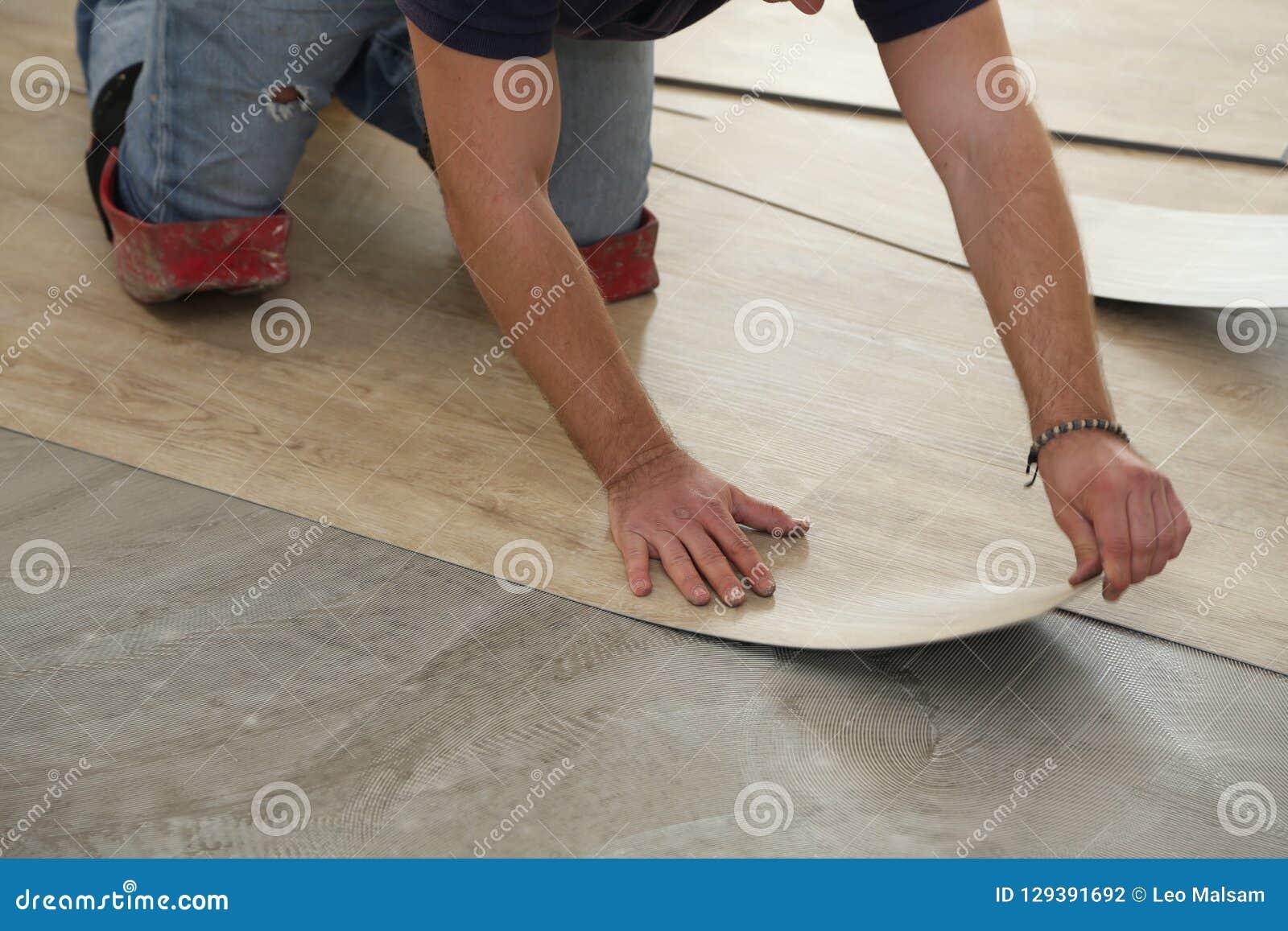Работа на класть настил Работник устанавливая новый плиточный пол винила
