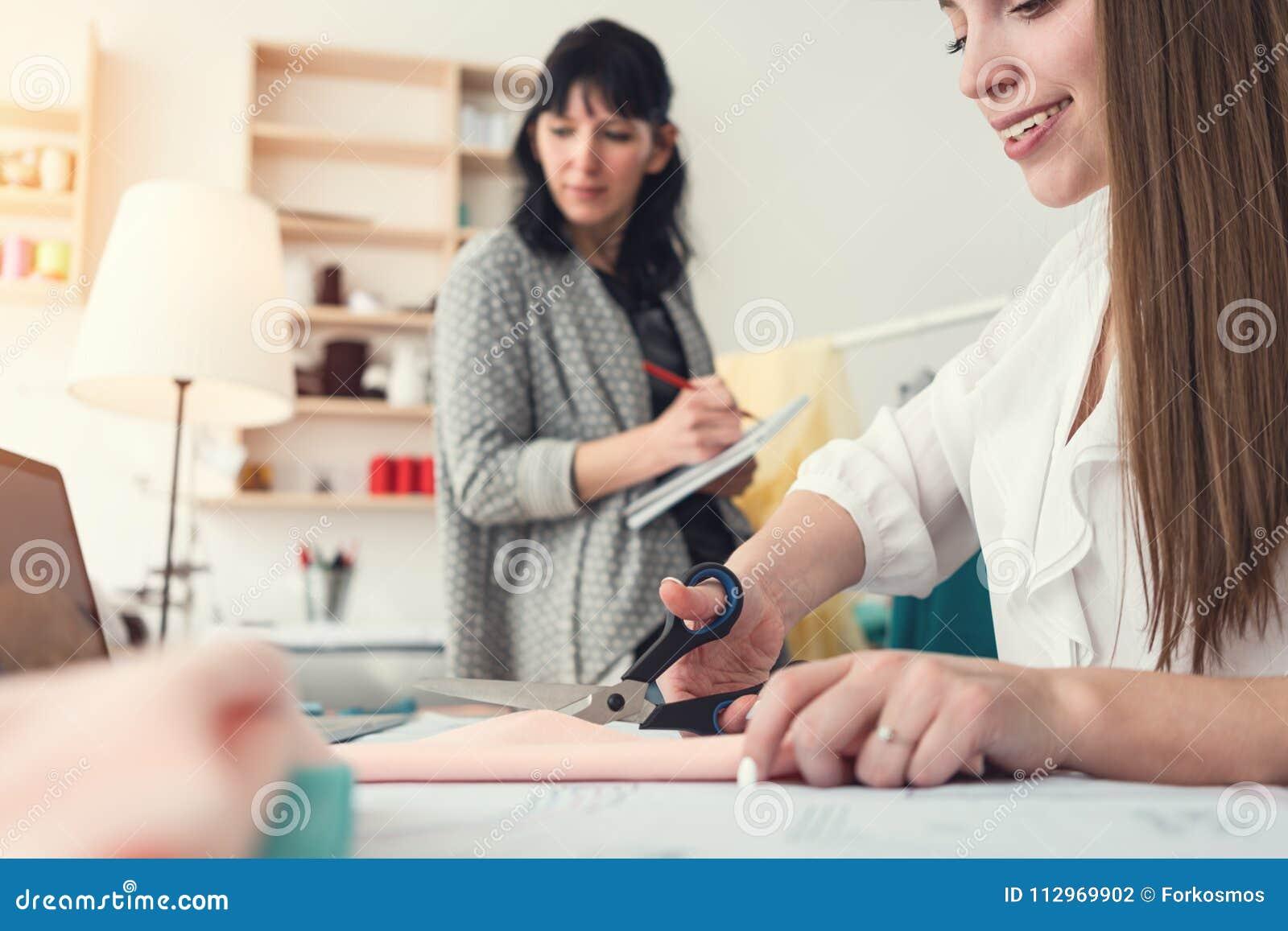 Работа отростчатая в шить студии 2 женщин dressmaker Зашейте мелкий бизнес Команда дизайнеров одежды шьет и создается