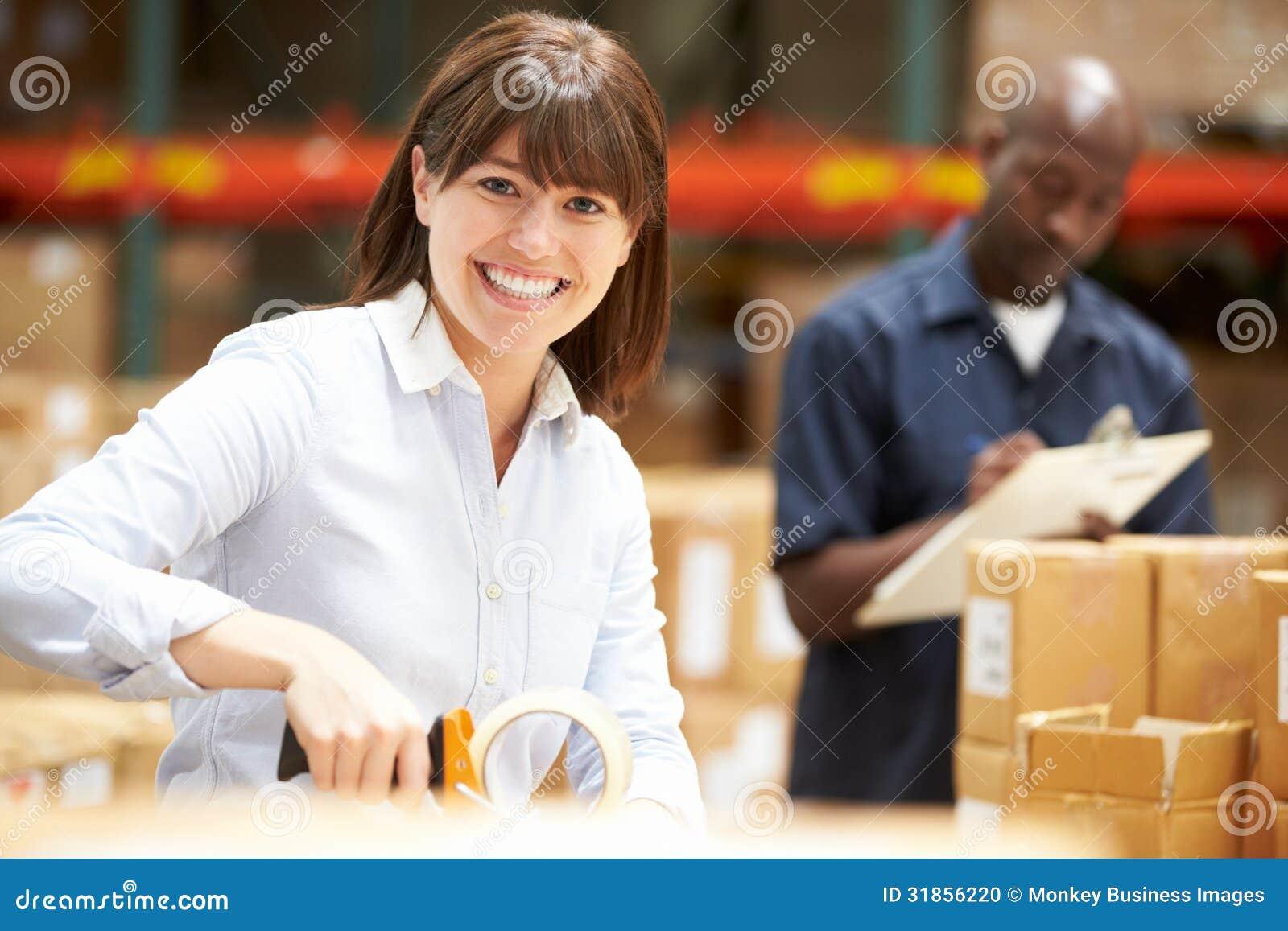 Работники в складе подготавливая товары для отправки