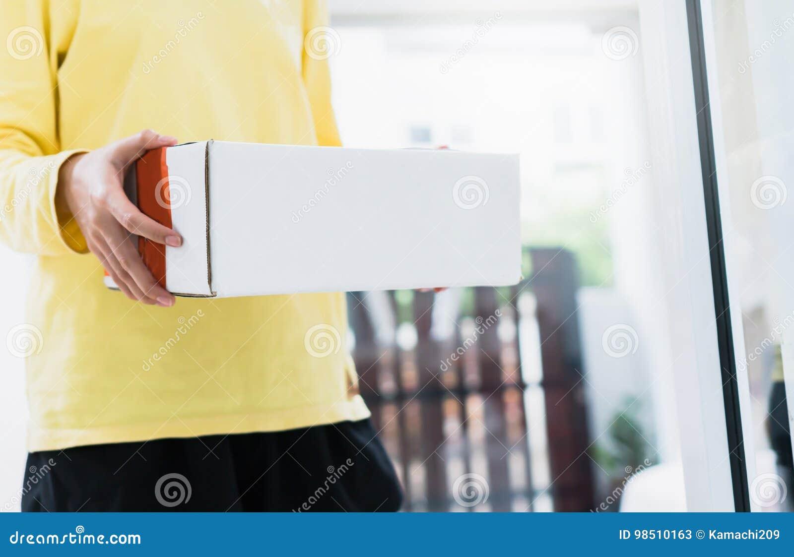 Работники держат пакет в автомобиле для посылки к клиенту Заказывание на линии для удобства клиентов