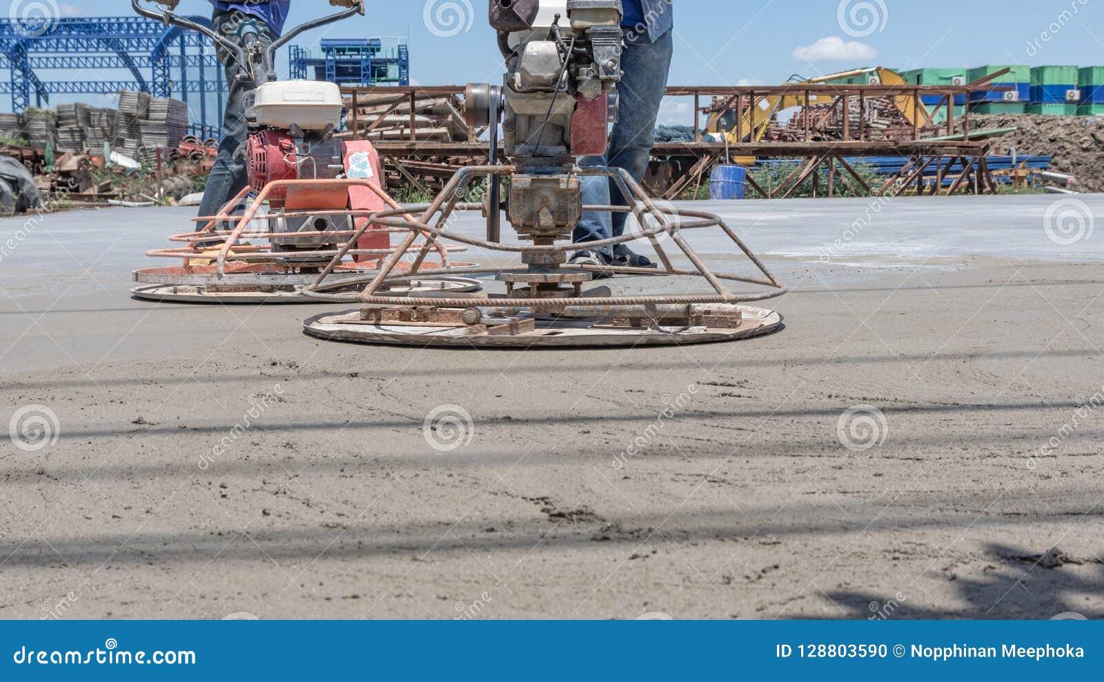 Работники используют конкретные полируя машины для цемента после лить готов-смешанный бетон
