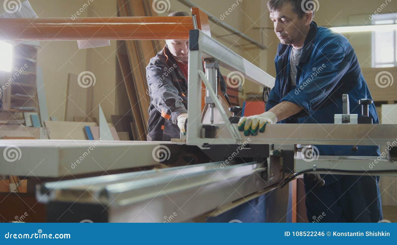 Работники на фабрике режут деревянную часть на электрической пиле на индустрии мебели